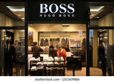 Shanghai/China-Oct.2019: facade of HUGO BOSS clothing store in Florentia Village Outlets. White brand logo.Illuminated clothing store inside. A German luxury brand.