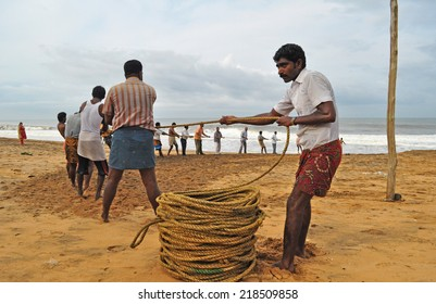 SHANGHUMUGHAM, TRIVANDRUM, KERALA, INDIA - MARCH 30, 2014: Fishermen hauling their catch still trapped in the fishing net. Visitors to the beach lend a helping hand. Tourism.