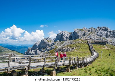SHANGRI-LA,CHINA-AUGUST 13,2019: Tourists walking on a wooden pathway To the Valley of Blue Moon viewpoint (Shika Snow mountain)