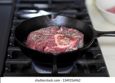Shank steak frying in a cast iron pan.
