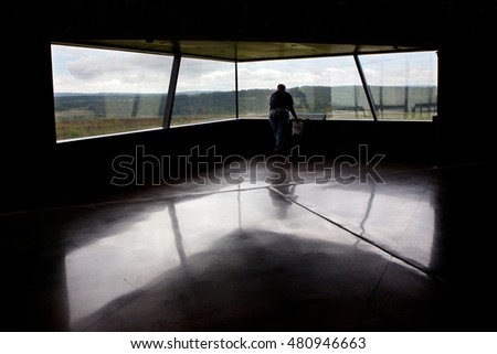 SHANKSVILLE, PA - AUGUST 17: An unidentified man looks through a window at the Flight 93 National Memorial Visitor Center near Shanksville, PA on August 17, 2016. The window overlooks the impact site.