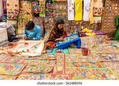 SHANTINIKETAN, INDIA - DECEMBER 25: An Indian artist couple paints colorful handicraft items for sale during the annual Poush Mela fair 2015 on December 25, 2015 in Shantiniketan, West Bengal, India.