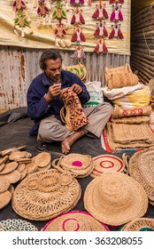 SHANTINIKETAN, INDIA - DECEMBER 25: An Indian artisan weaves creativel handicraft items for sale during the annual Poush Mela fair 2015 on December 25, 2015 in Shantiniketan, West Bengal, India.