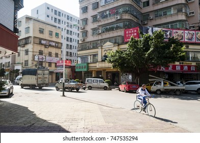 SHANTOU, CHINA - OCTOBER 23, 2017: a boy riding a bike to school on the road surrounded with tall apartment in chenghai district