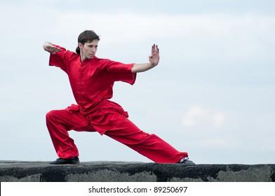 Shaolin warriors wu shoo man in red with sword practice martial art outdoor. Kung fu