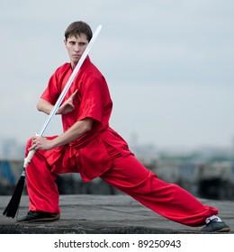 Shaolin warriors wu-shoo man in red practice martial art outdoor. Kung fu