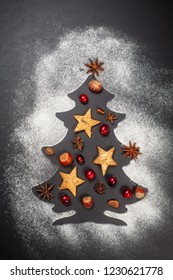Shape of Christmas tree on dark background with nuts, cranberries