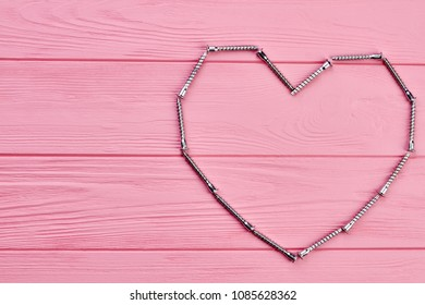 Shape of heart made from hardware. Valentines holiday background with heart shape made from metal fastener, copy space.
