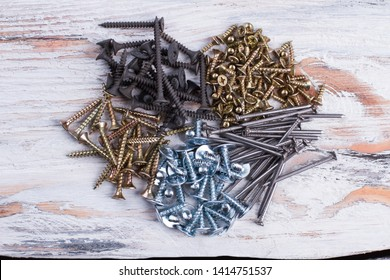 Shape of heart made from screws. Various screws and nails forming heart shape on wooden background.