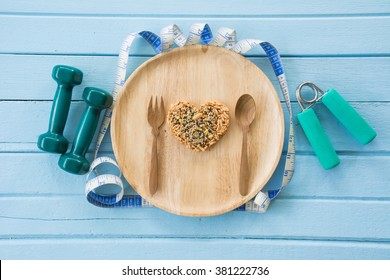 Shape Heart made from whole grain on wooden dish, fork and spoon and  dumbbell fitness on Wooden table, Top view