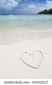 The shape of a heart in the sand of a clean white beach with turquoise water