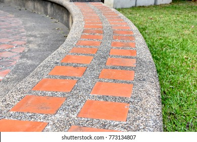 Shape of long curved seat at the outdoor park made concrete with stone and orange square ceramic tiles.