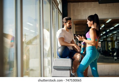 Shape sporty beautiful girl flirting with a muscular guy next to her while standing near the window in the gym.