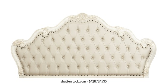 Shaped pastel beige color soft tufted leather capitone bed headboard of Chesterfield style sofa with carved wooden frame, isolated on white background, front view