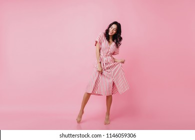 Shapely barefooted lady with tanned skin dancing on pink background. Happy caucasian girl in striped dress fooling around and laughing.