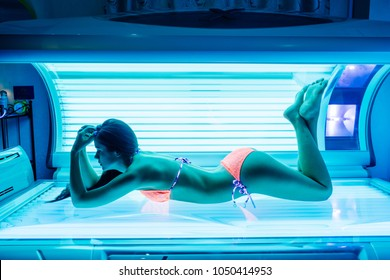 shapely beautiful young girl sunbathing in a solarium, wants a beautiful tanned skin