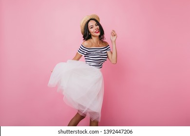 Shapely brunette lady in hat dancing with pleasure. Ecstatic female model in lush skirt and striped t-shirt having fun.