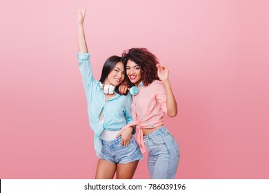Shapely european woman with bronze skin dancing with hands up near black female friend. Charming ladies in jeans and cotton shirts relaxing in pink studio.