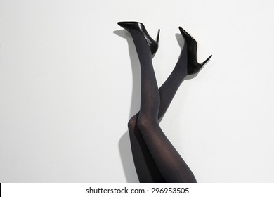 Shapely female legs. Beautiful, leggy woman in thin tights and fashionable styling