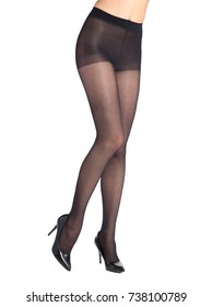 Shapely female legs dressed in dark tights. Isolated on white background