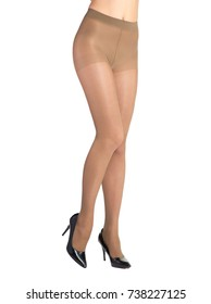 Shapely female legs dressed in tights body color. Isolated on white background