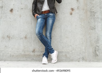 Shapely female legs in sneakers and jeans near a concrete wall