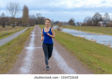 Shapely fit young woman working out in winter running towards the camera along a wet country road alongside a river in a healthy lifestyle concept