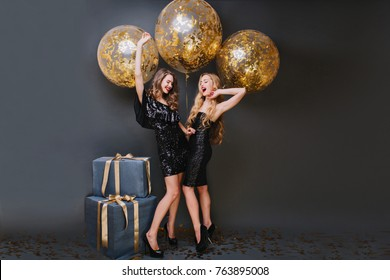 Shapely girl with long curly hair fooling around with sister during birthday photoshoot on black background. Enchanting ladies in trendy dresses waiting for party, standing near gifts.