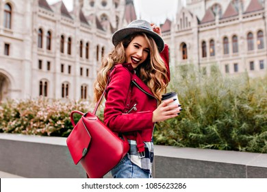 Shapely girl with wavy hair laughing while exploring old part of city. Charming female tourist in hat holding cup of coffee and smiling.