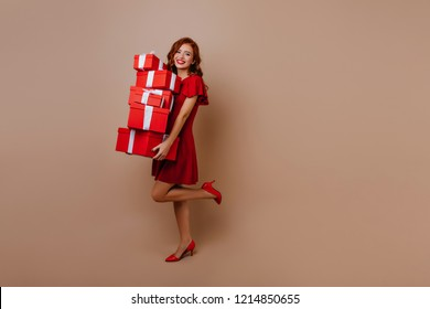 Shapely lady on high heel shoes celebrating birthday. Good-humoured ginger girl with new year gifts expressing happiness.