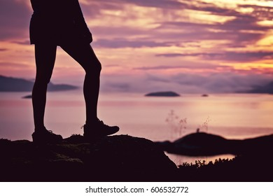 Shapely legs girls hiking silhouette in mountains, sunset and ocean, fjords. Woman hiker with backpack on top of mountain looking at beautiful night landscape, fog in the mountains.
