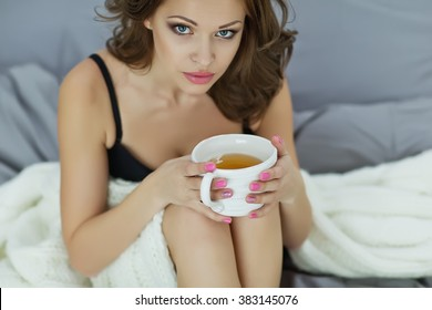 Shapely legs sitting on a bed with a light bed in a warm and cozy bed.Hand and cup.A woman and a bed.A woman sitting on a bed in her hands a cup of hot tea,she reads a book.The long legs and the bed.