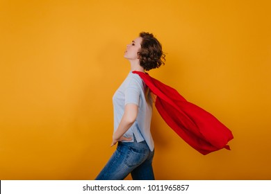 Shapely young lady with red cloak waving standing in studio. Confident superwoman in jeans and mantle posing on yellow background.