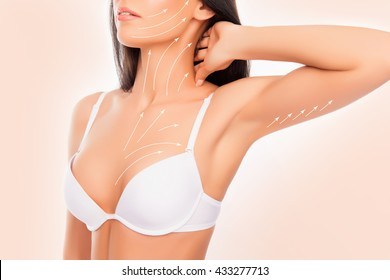 shapely young woman with perfect body with the drawing arrows wearing white bra, touching her neck