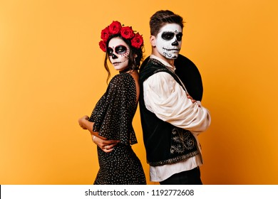 Shapely zombie girl in black dress posing in studio with boyfriend. Indoor photo of good-looking couple with skull makeup.