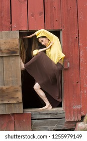 Shapes of a dancer in Earth tones complement a doorway in the side of a red barn on a farm in Ellington, Connecticut.