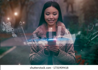 Shaping the future of urban living, a woman in the park is using a holographic display to multitask through various apps in her phone, projected as augmented reality around her.