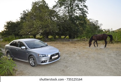 Shapsugs, Russia - July 30, 2016: Due to human movement. Car and horse. Iron horse and ordinary. Symbolism sredst transport.