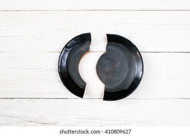 Shards of a broken black plate on white wooden surface.  Problem, accident, divorce, misfortune, scandal, quarrel concept. Flat lay of contrast black broken on two parts plate.