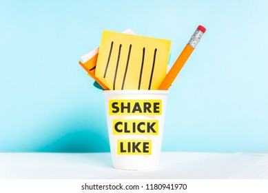 Share click like words. Paper cup with post-it notes and pencil on blue background over desk.