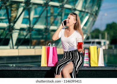 Share a discount with friends! Joyful girl with bright shopping packages speaks on the phone. The final big summer and autumn sale