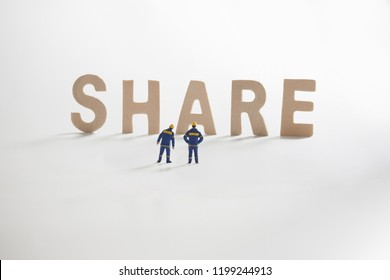 SHARE word  with Miniature people: Engineer standing infront use as business concept.
