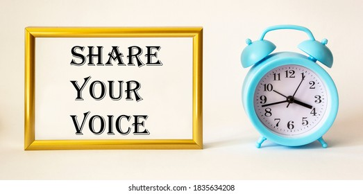 Share your voice written on gold photo frame next to alarm clock on white background.