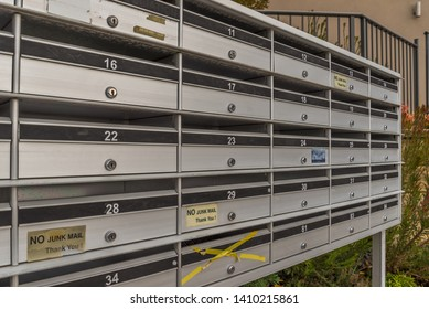 Shared modern metallic mail boxes in shared common area space of condominium apartment flat unit