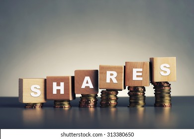 shares text written on wooden block with stacked coins on grey background