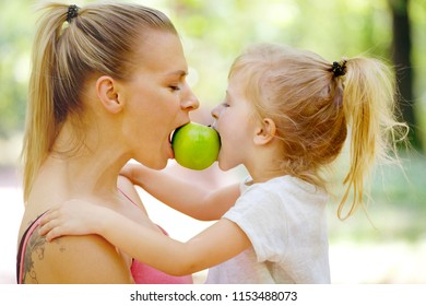 Sharing an apple. Mother and daugher eating fruit. Family life, healthy eating