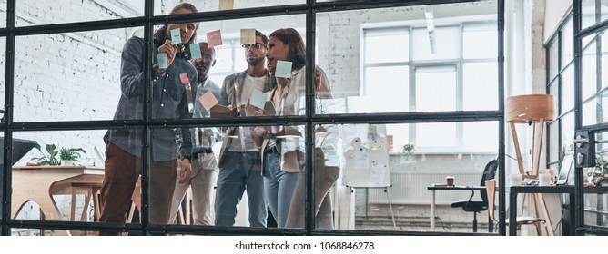 Sharing business ideas. Full length of young modern people in smart casual wear using adhesive notes while standing behind the glass wall in the board room