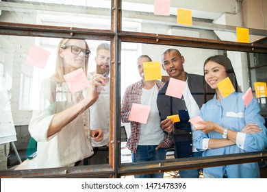 Sharing business ideas. Young modern people in smart casual wear using adhesive notes while standing behind the glass wall in the board room