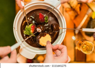 Sharing a chocolate fondue dessert with friends