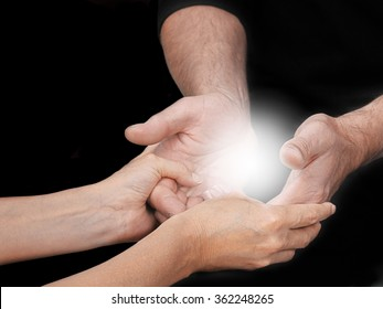 Sharing an Energy Experience - female healing mentor holding male students open hands with a bright light energy orb between on a black background and copy space